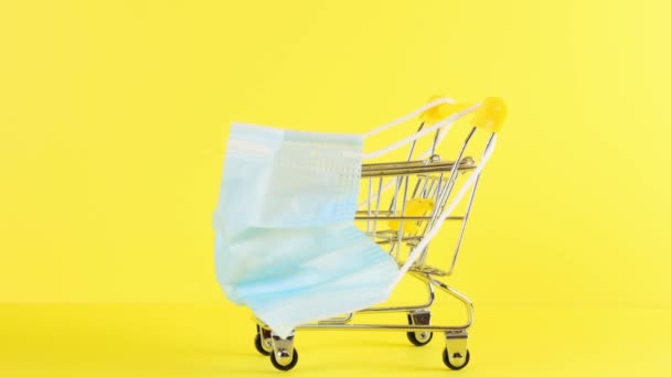 Shopping cart and medical protective mask on a yellow background, closeup. Black Friday Shopping and Discount Concept. Concept of protection against viruses and other diseases, medicine.