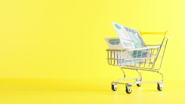 Shopping cart with 1000 rubles banknote on a yellow background, closeup. Black Friday Shopping and Discount Concept