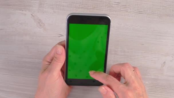 Die Hände einer Seniorin mittleren Alters bedienen ein Smartphone-iPhone mit Chroma-Schlüsselbildschirm, Kopierfläche. Online-Shopping-Konzept, Nutzung mobiler Anwendungen: Moskau, Russland - 24. Juni 2021.