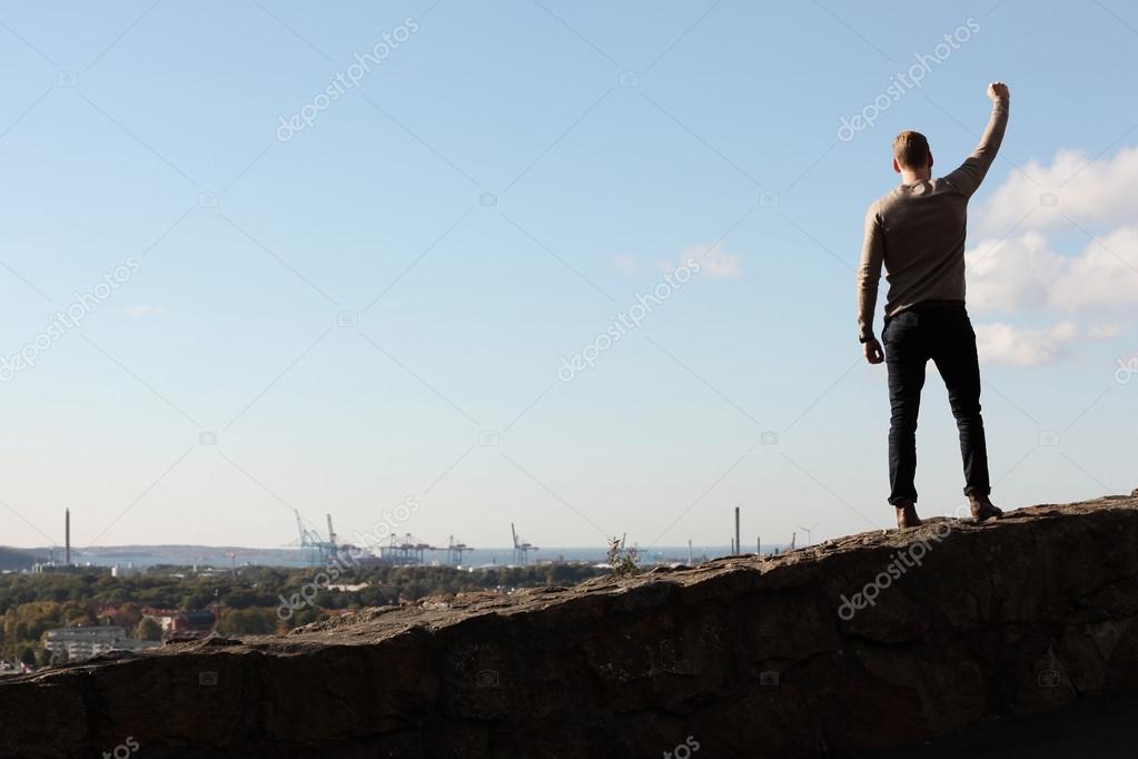 Man on top of mountain cityscape