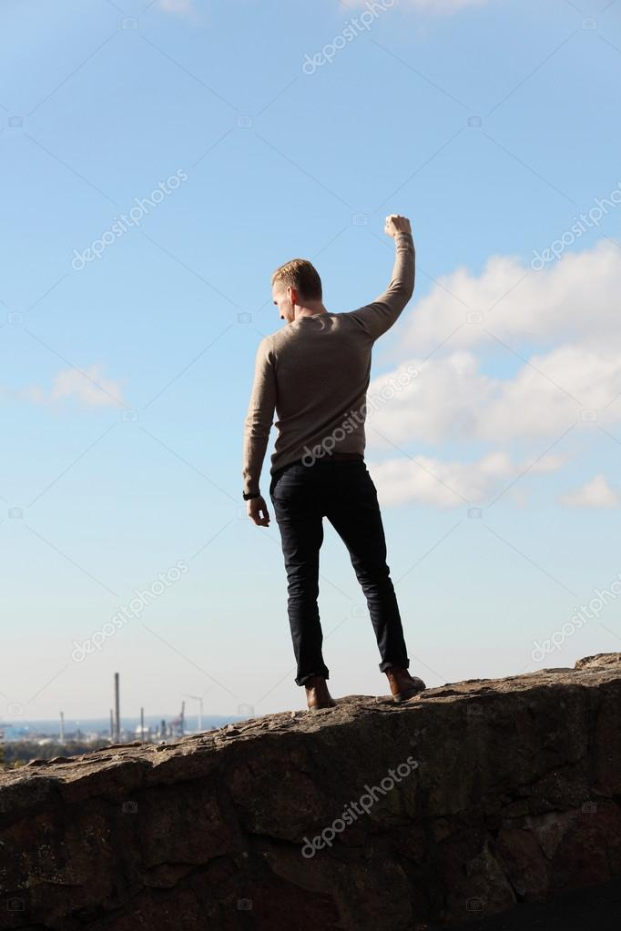 Man on top of mountain cityscape