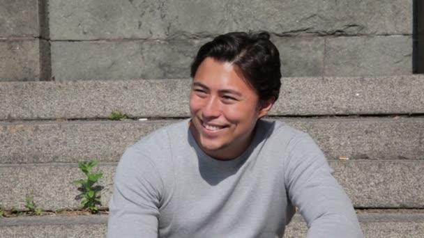 Uvolněné mladý muž sedí se venku za slunečného dne