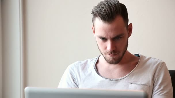 Attractive man sitting down with laptop
