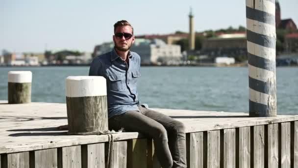 Pohledný muž sedí v přístavu