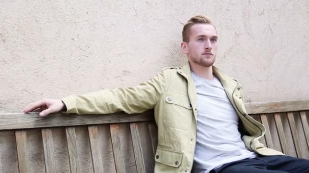Az ember ül le egy padon a szabadban