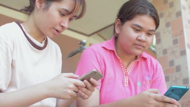 Két thai tini nővérek alkalmi ruha élvezze a csevegést a szociális kommunikáció online okostelefonnal, miközben ül a házuk előtt. Ázsiai testvér. Összetartozás a mobiltechnológiával.