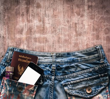 Blue jeans with cell phone, flashlight and passport in a pocket