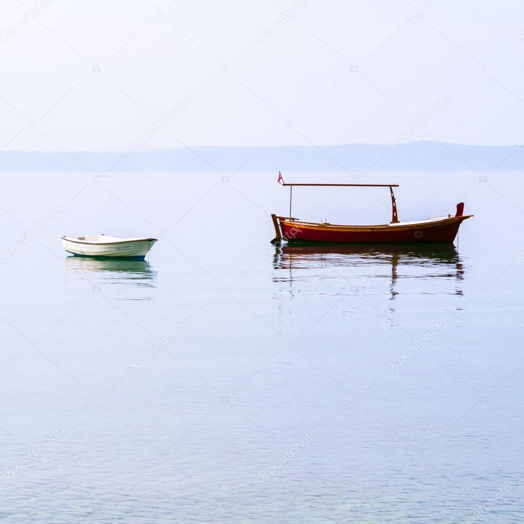 Two boats on calm water in the early morning in Dalmatia