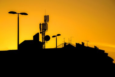 Roofs of buildings with many antennas in a big city at sunset ma