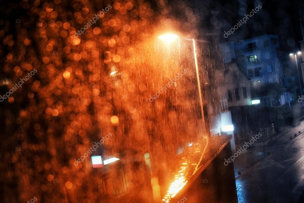 Rain drops on the window with dark streets outside and street lights shining
