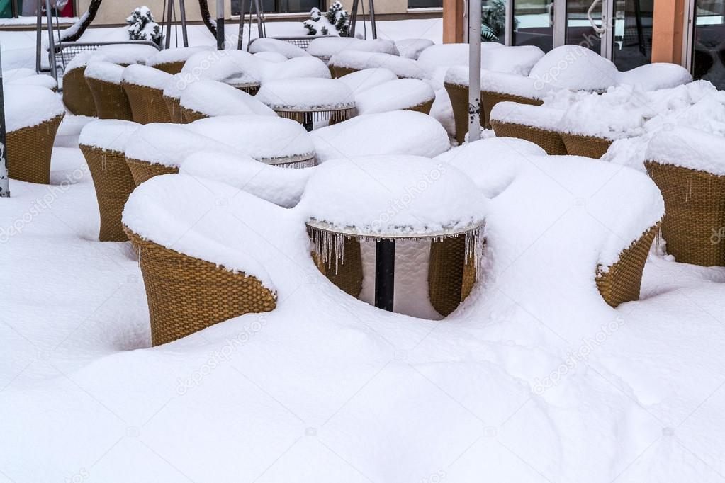 Tables and chairs in front of restaurant buried in snow