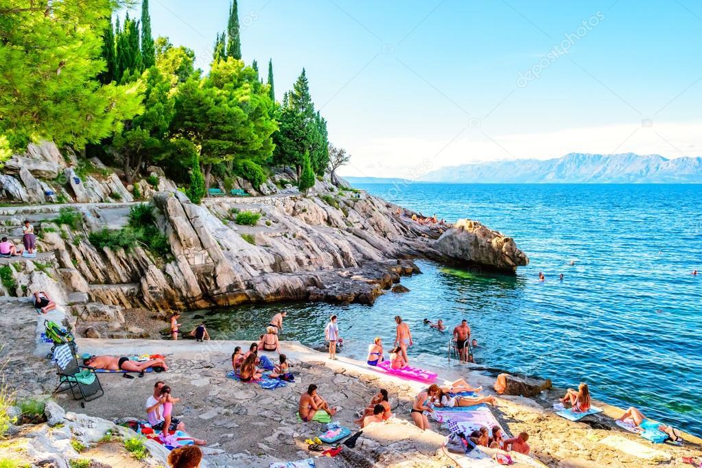 TRPANJ, CROATIA - AUGUST 6, 2014: People swimming and sunbathing on the rocks in southern Croatia.