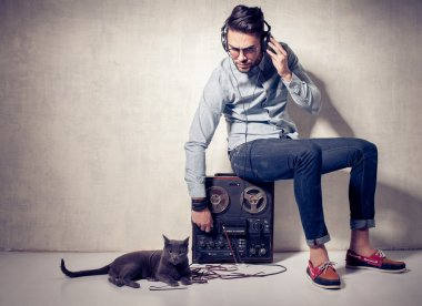 Handsome man and cat listening to music on a magnetophone against grunge wall stock vector