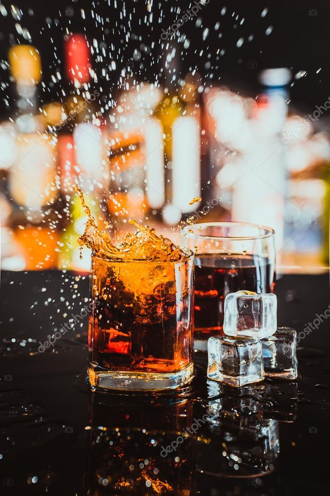 two glasses of whiskey on a blurred background bar