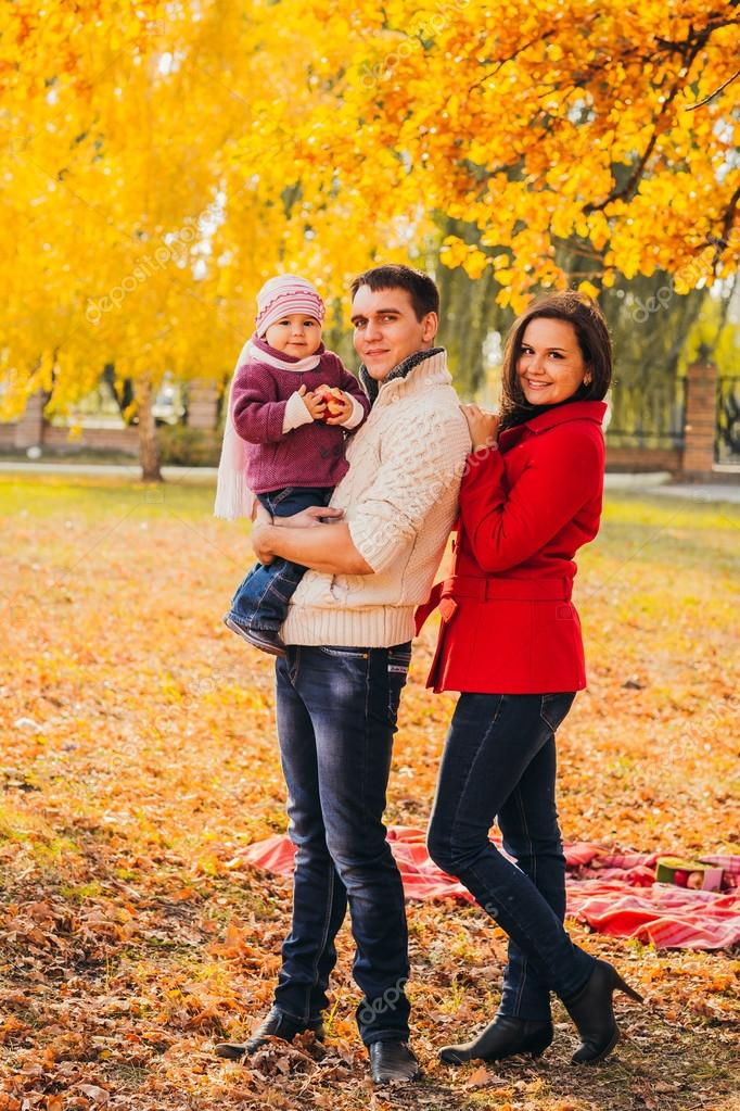 Picture of lovely family in autumn park, young parents with nice adorable kids playing outdoors, five cheerful person have fun on backyard in fall, happy family enjoy autumnal nature