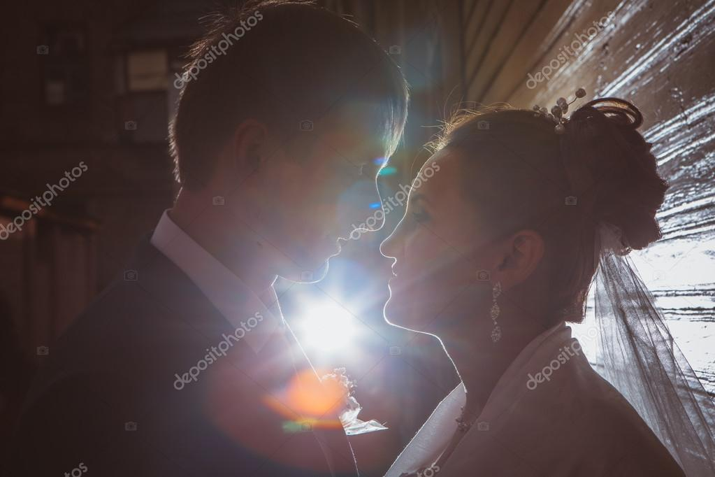 Silhouettes of a beautiful wedding couple in the dark background. Retro or vintage style.