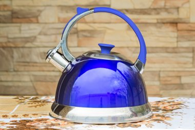 Bright blue kettle on the tablecloth table.