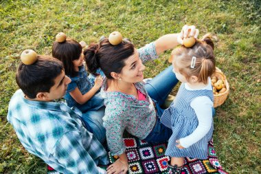 Happy family of four lying in the grass playing with apples in a