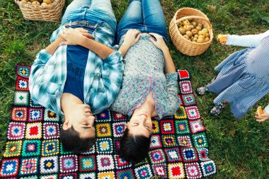 Couple resting on a blanket on the grass in autumn and todler de