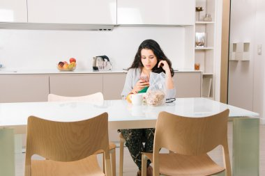Girl using phone while breakfast in the kitchen