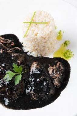Squid in ink with rice and parsley