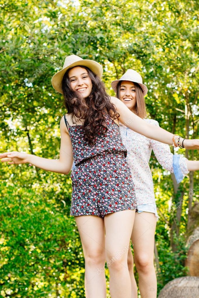 Cute girls walking on a tree trunk