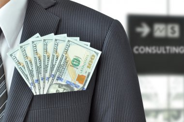 Dollar banknotes in pocket of businessman's suit