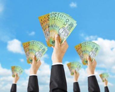 Hands holding Australian dollar banknotes