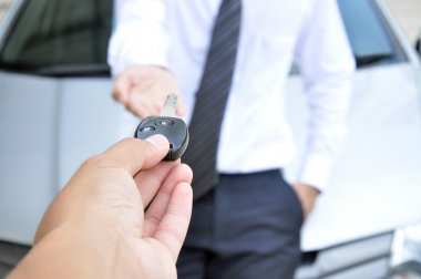 Hand giving a car key to another man