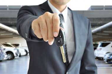 Businessman hand giving a car key - car sale & rental business concept