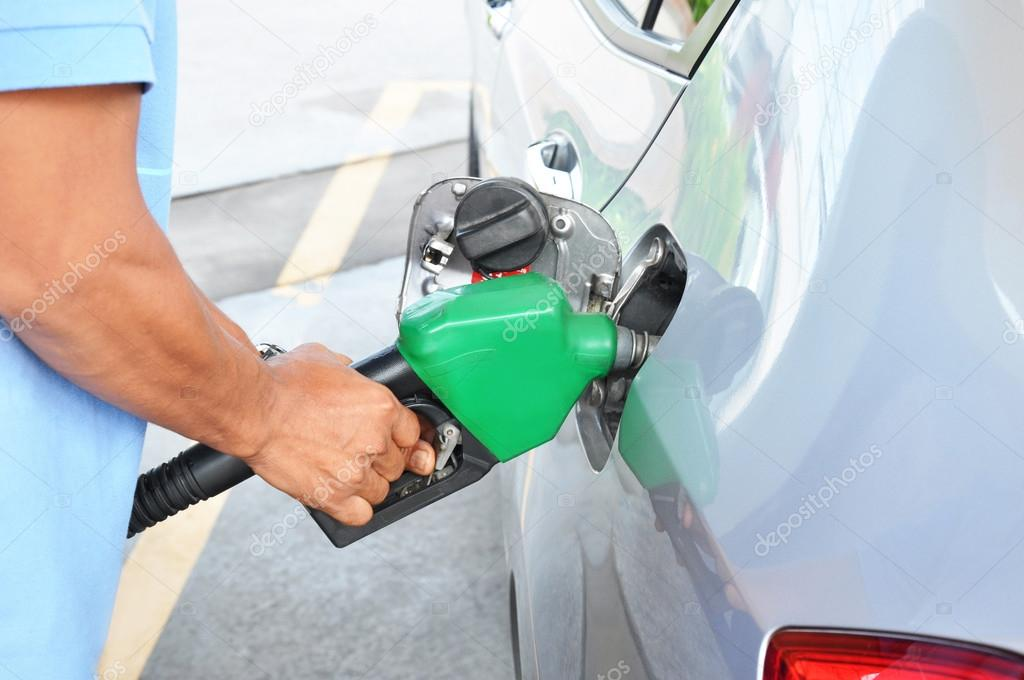 A man filling up the gas tank of a car