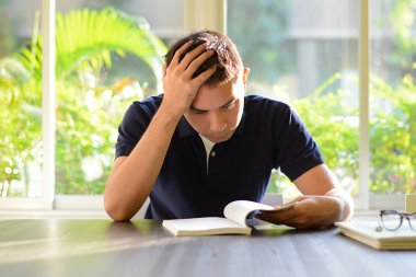 Stressed man reading book with hand on his head