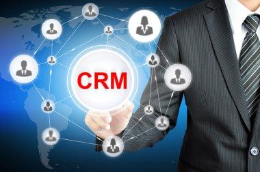 Businessman pointing on CRM (Customer Relationship Management) sign