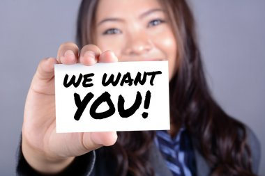 WE WANT YOU! message on the card shown by a businesswoman