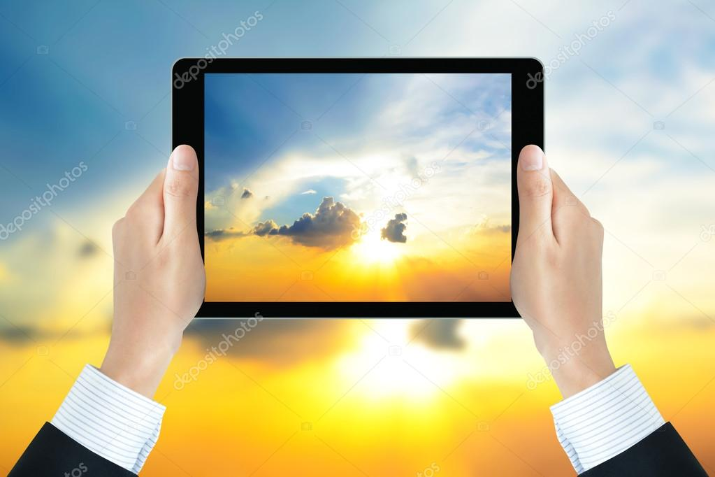 Businessman hands holding tablet pc, taking picture of the sun shining in the sky