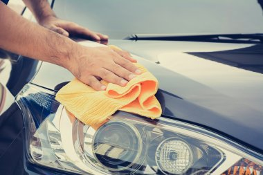 A man cleaning car with microfiber cloth, car detailing (or vale