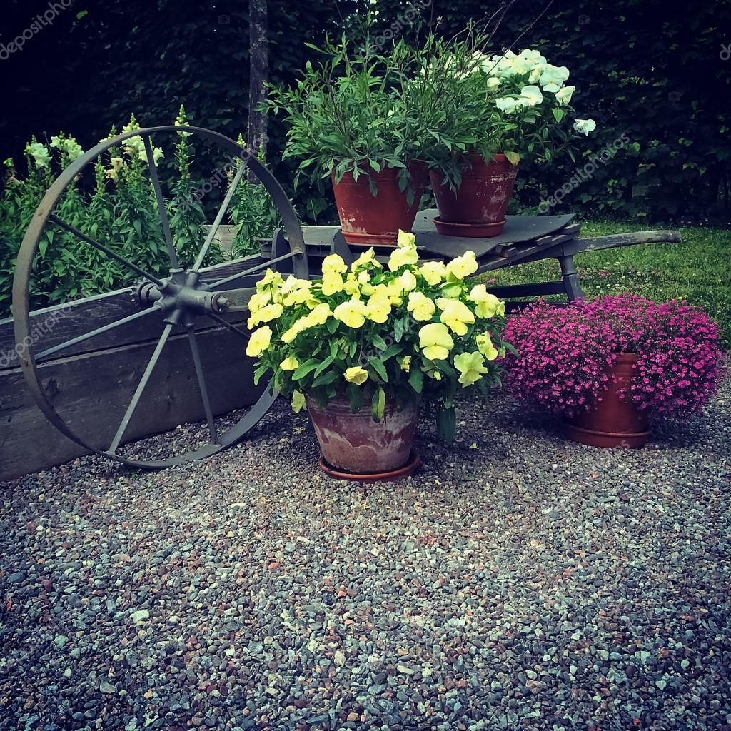 Garden decorated with flowers and old wheel