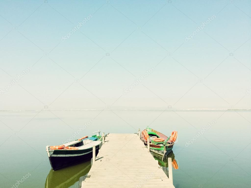 Calm lake with two fishing boats