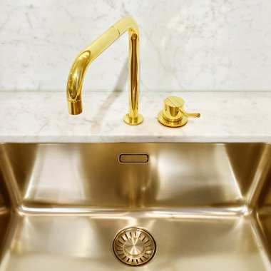 Kitchen sink with golden faucet