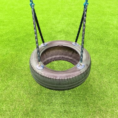 Tire swing on green grass background