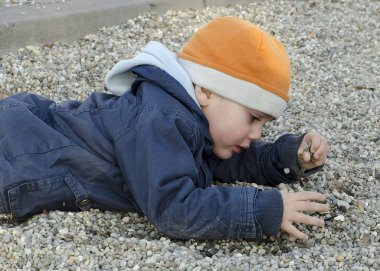 Child playing with pebbles