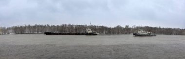barge and pleasure boats sail along river in early spring against background of forest. Panoramic view.