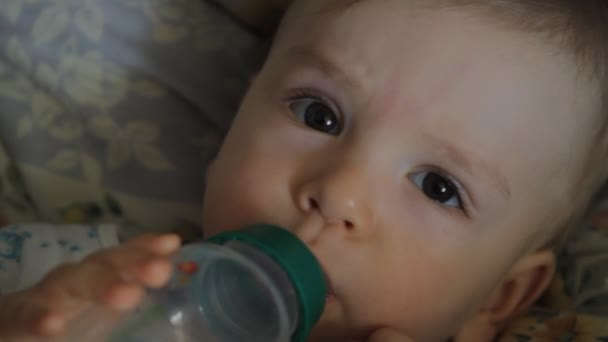 baby drinks juice from a bottle, close-up portrait
