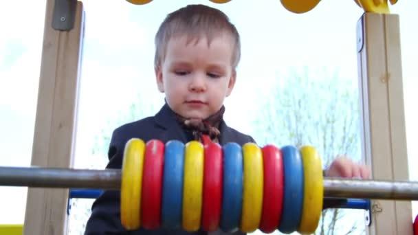 Malý chlapec hraje s počitadlo. Dětský park
