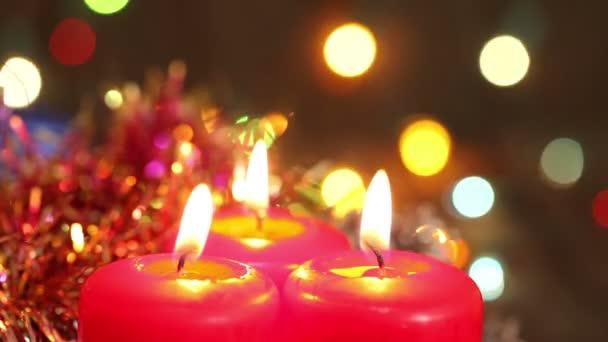 Tre candele burning di Natale circondate da ghirlanda lampeggiante. Priorità bassa
