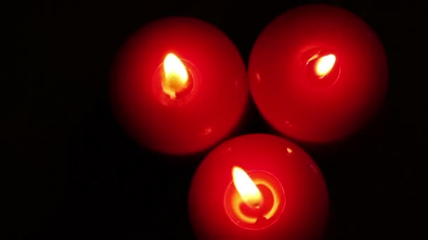 Three burning Christmas candles. Blurred background with Christmas garland