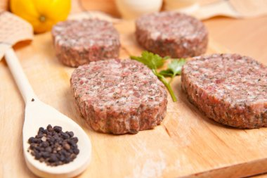 Raw burgers on a cutting board with lemon wedges
