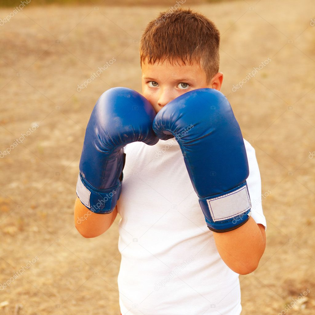 Boy with boxing gloves posing in the forest outdoors