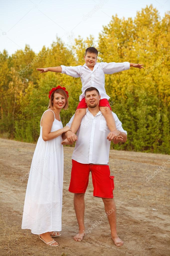 mom dad and son posing at the park outdoors