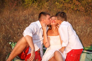 Dad and son kissing his mother on the cheek on both sides, in th